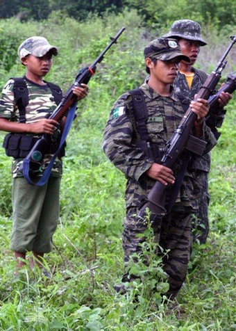 A young Muslim separatist rebel of the Moro Islamic Liberation Front is seen carrying a firearm and ammunition pack in a formation together with other guerrillas at a rebel camp in Shariff Kabunsuan province in southern Philippine island of Mindanao, 19 May 2007.  Children in the Philippines are willingly joining communist or Muslim separatist guerrilla groups to escape grinding poverty, a UNICEF commissioned study released 5 December 2007 said.  The Ibon Foundation, which carried out the study, found fear of the military, poverty and limited social services were pushing some children to join the communist New People's Army (NPA) and the Moro Islamic Liberation Front (MILF). AFP PHOTO/MARK NAVALES (Photo credit should read MARK NAVALES/AFP/Getty Images)