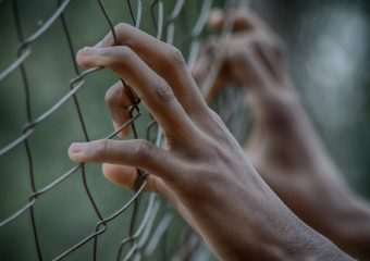 Stock photo of prisoner behind fence