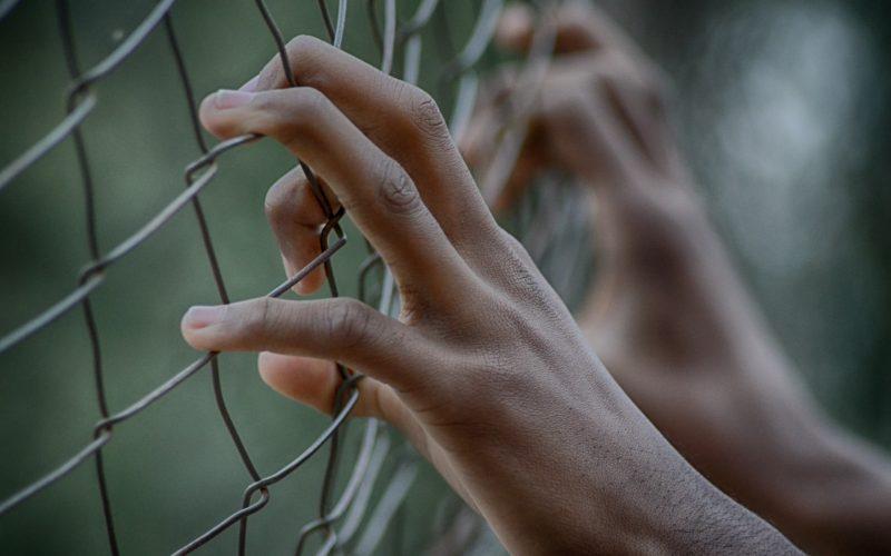 Stock photo of prisoner behind fence